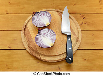 Red onion cut in half with a knife on a cutting board