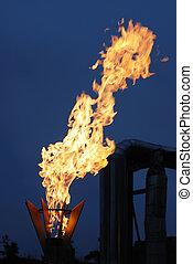 burning torch against industrial dusk background