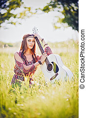 Portrait of pretty young hippie girl with guitar. Outdoor...