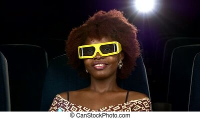 Portrait of smiling African American watching woman movie in theater. 3D glasses