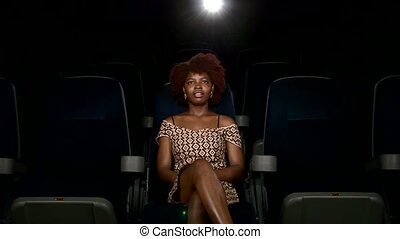 Portrait of smiling African American watching movie in theater