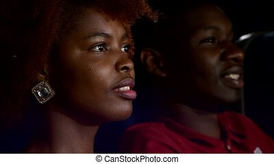 Happy African American couple, watching movie In theatre,...