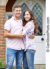 Portrait Of Loving Couple Standing Outside Home