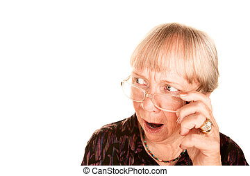 Shocked senior woman looking over the top of her glasses -...