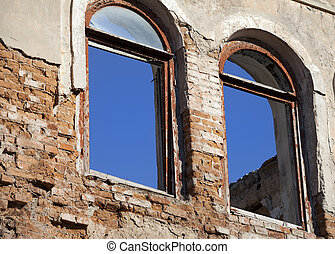 Brick wall of old destroyed house with broken windows