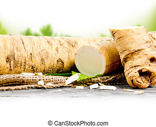Horseradish - Photo of horseradish root with slice on burlap...