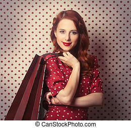 Portrait of a redhead girl with shopping bags on polka dot...