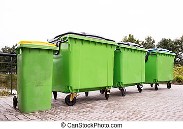 Greeen garbage containers in a row along street
