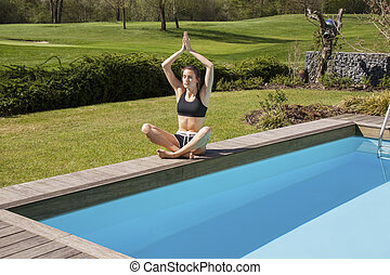Young woman meditating at the side of a pool sitting cross...