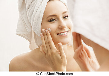 Woman Applying Cream on Face After Shower