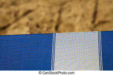Deckchair in strict closeup, with sand of beach on the...