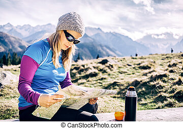 Woman checking map hiking in mountains - Young woman hiker...