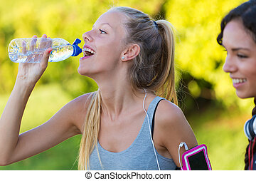 Running girl drinking water after running. - Outdoor...