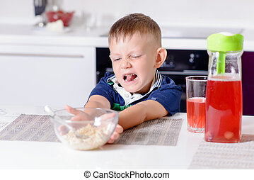 Boy Pushing Away Bowl of Cereal at Breakfast - Blond Boy...