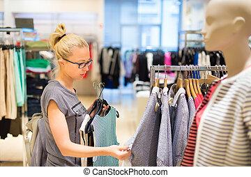 Beautiful woman shopping in clothing store. - Woman shopping...