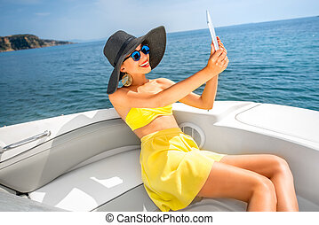 Woman relaxing with digital tablet on the yacht - Young...
