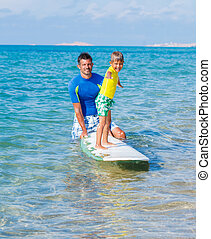 Boy surfing - Little boy with his father learning surfing