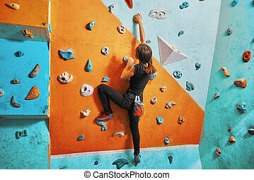 Woman climbing up on practice wall - Young woman climbing up...