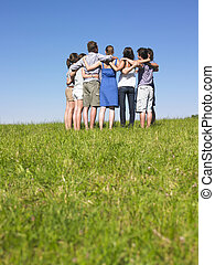 Group of People in Huddle in Field - A group of people...