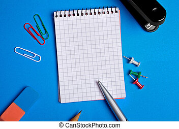 Empty notebook with office supply on background
