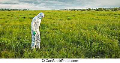Scientist in protective uniform on summer field - Male...