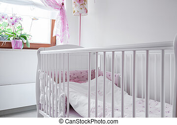 White crib in nursery room