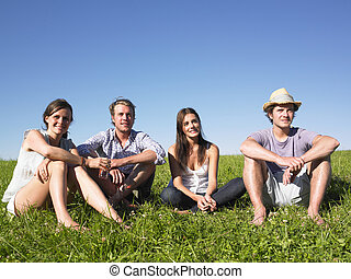 Four People Sitting on the Grass - Two men and two women...