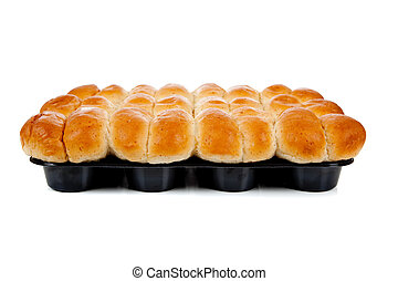 A dozen cooked rolls in a pan on white