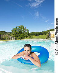 Smiling Woman Floating in Pool - Woman floating in inner...