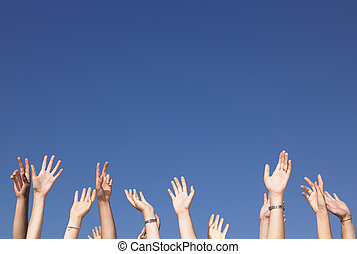 Arms Raised Against Blue Sky - Cropped view of group of...
