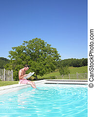 Man Reading at Edge of Swimming Pool - Man reading a...