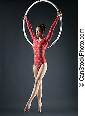 Elegant young girl dancing on aerial hoop - Studio shot of...