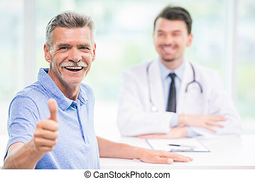 Doctor and patient - Smiling male patient sitting at...