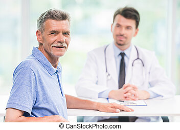 Doctor and patient - Smiling male patient sitting at doctors...