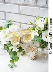 Two vintage glasses of champagne and white flowers, candles...