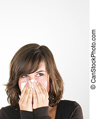 Young Woman Blowing Nose - Young woman with cold blowing...