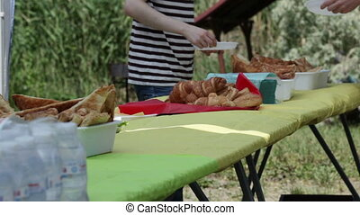 Picnic food distribution - On small table people take cakes