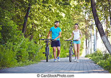 Couple of bicyclists - Active couple with bicycles walking...