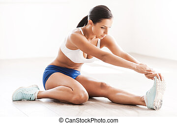 Stretch for success. Beautiful young woman in sports clothing doing stretching exercises while sitting on the floor
