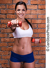 Strengthening her muscles. Beautiful young woman in sports clothing exercising with dumbbells and smiling while standing against brick wall