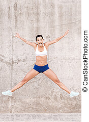 Happy to live fit and healthy. Beautiful young smiling woman stretching out arms and legs while jumping in front of the concrete wall