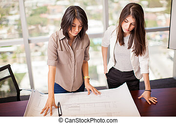 Business partners looking at a plan - Couple of female...