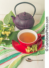 Red cup of linden tea and teapot on white wooden background