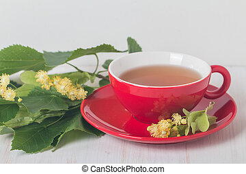 Red cup of linden tea on white wooden background