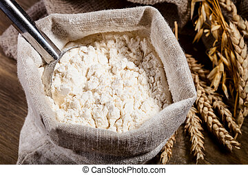 Flour in burlap sack with scoop of metal