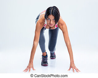 Runner sporty woman in start position over gray background....