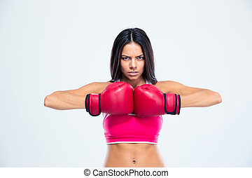 Sporty woman in boxing gloves looking at camera over gray...