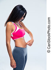 Fitness young woman touching her belly fat over gray...