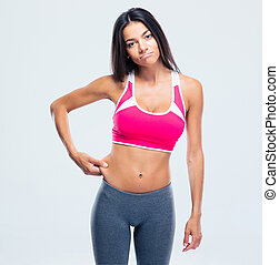 Fitness woman touching her belly fat over gray background