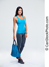 Happy sporty woman holding backpack - Full length portrait...